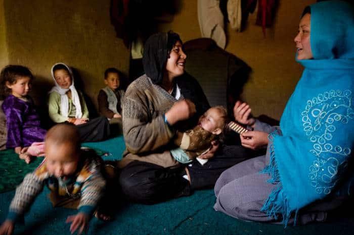 Community Health Worker Ozara Husseini talks to Najiba, who has five children. Kate Holt.