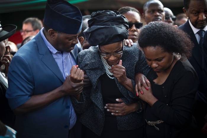 The mother of President Kenyatta's nephew Mbugua Mwangi is comforted by family members at his graveside. Kate Holt.