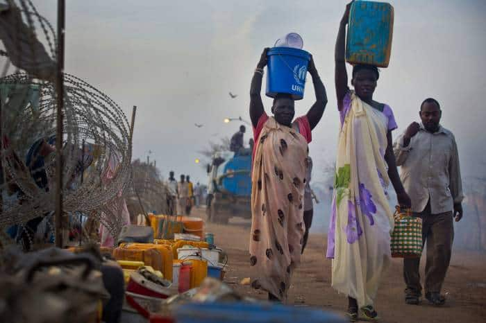 Women displaced by recent fighting between rebel soldiers and government troops carry water containers. Kate Holt.