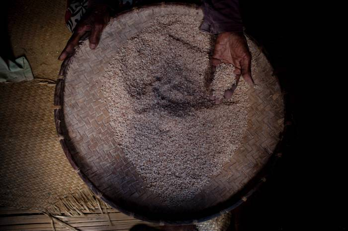 An elderly woman sifts through rice at her home in the village of Androranga Vola. Kate Holt.