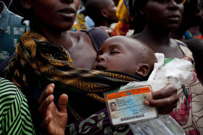 A woman waits with her election card to receive a food ration in Mugunga camp in Goma. Kate Holt.