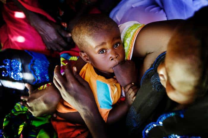 A woman breastfeeds her baby at a community mobilisation meeting. Kate Holt.