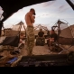 A soldier from the Royal Engineer Regiment lights a cigarette in the evening light. Kate Holt.