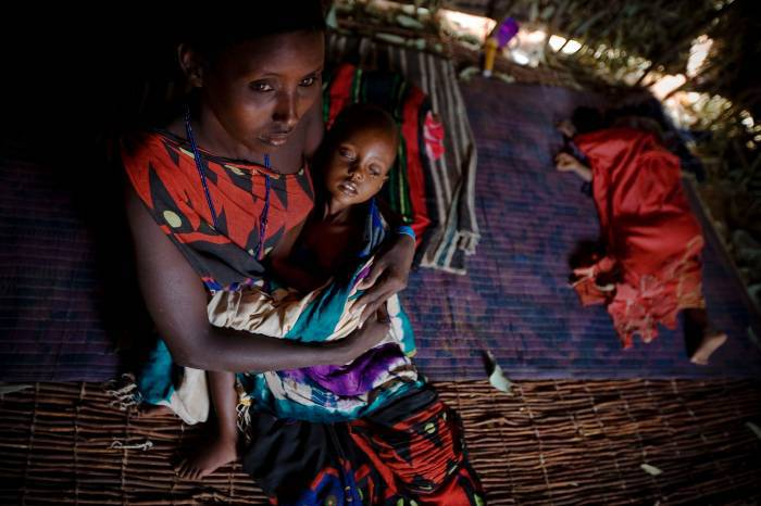 Shangara Hassan, who is 20 years old and has four children, holds her sick daughter. Kate Holt.