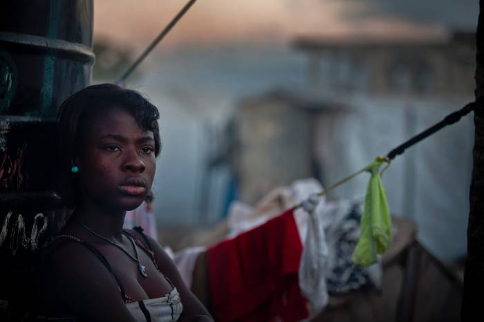 A girl poses for a photograph who is still living in a camp in Port au Prince. Kate Holt.