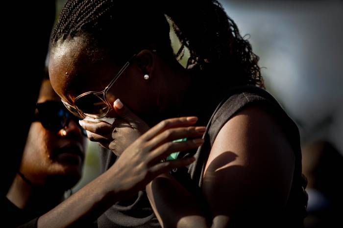 A mourner is comforted at the graveside of President Kenyatta's nephew Mbugua Mwangi and his fiancee. Kate Holt.