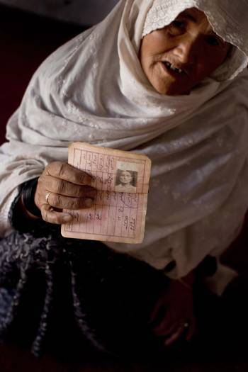 An elderly woman holds up the identity document of her husband who disappeared last year near their home. Kate Holt.