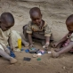 Neema Moshi's little sister Eva and her two little cousins play with old bottle tops. Kate Holt.