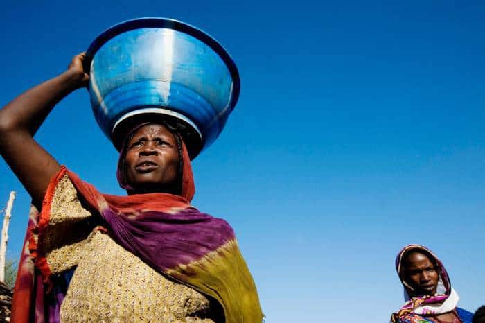 A woman carries water on her head in the evening light at a settlement for displaced people. Kate Holt.