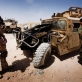A soldier from the ANA (Afghan National Army) and a Danish Soldier view the remains of a Humvee. Kate Holt.