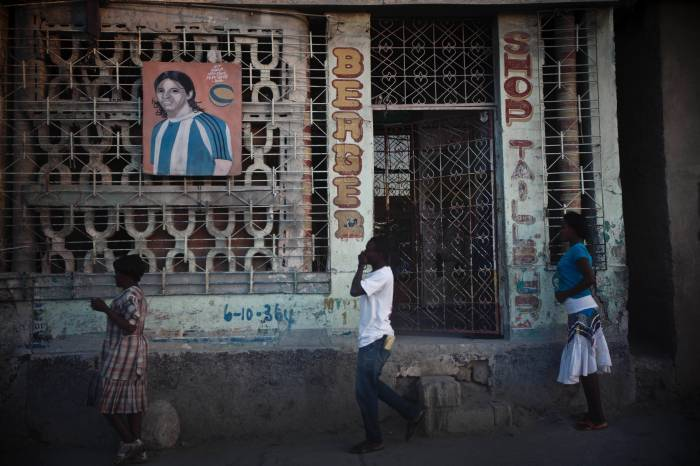 People walk passed a boarded up shop in downtown Port au Prince, Haiti on the 14th January, 2013. Kate Holt.