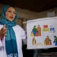 Community midwife, Sadiqa Hosseini, holds up an educational picture book. Kate Holt.