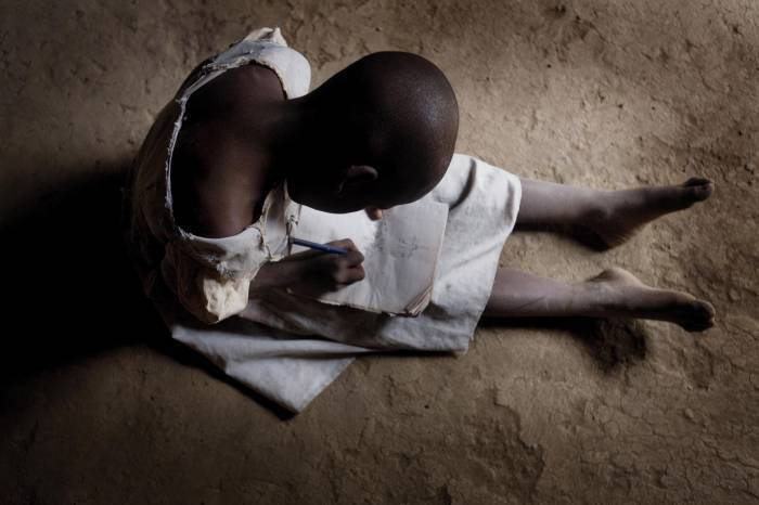 Neema Moshi writes in her exercise book at home during the holidays in the town of Makuyuni. Kate Holt.