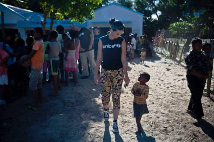 Katy Perry walks with a little boy she has just met at the end of a visit to the Tamatave Youth Center. Kate Holt.