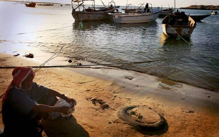 A Somali man sits near the port in Bosasso, Somalia, looking out over some of the boats. Kate Holt.