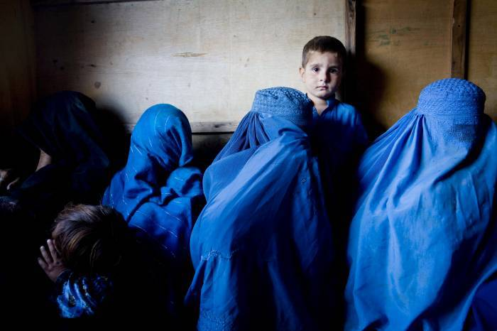 A young boy waits with his mother who is attending a talk on the importance of vaccination. Kate Holt.
