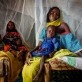 A mother, who is a refugee from Darfur, cradles her young baby in her lap. Kate Holt.