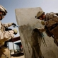 1st Lt Conner Gentil of 2/2 of the US Marine (R) and one of his soldiers washes off newly painted graffiti. Kate Holt.
