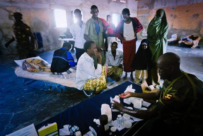A Ugandan doctor working for AMISOM administers drugs in a temporary clinic. Kate Holt.