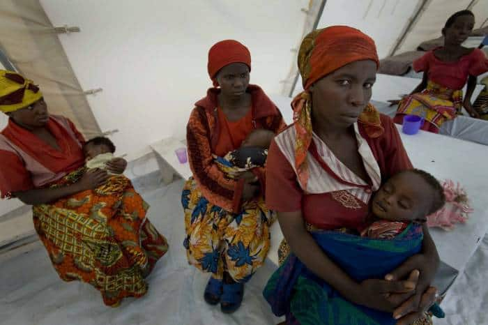 Women who have been displaced by recent fighting wait with their young children who are suffering from cholera. Kate Holt.