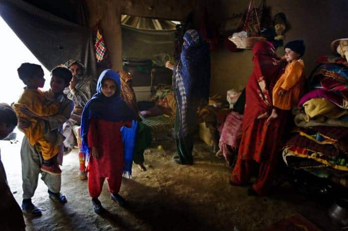 The family of Sulaman and Gulmana stand in their home that they have built. Kate Holt.