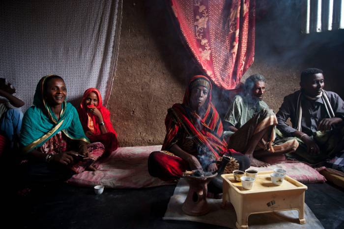 Members of a women's group that is supported by APDA drink coffee in a member's house near Logya. Kate Holt.