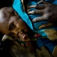 A woman puts her hand on her malnourished child in a therapeutic feeding centre. Kate Holt.