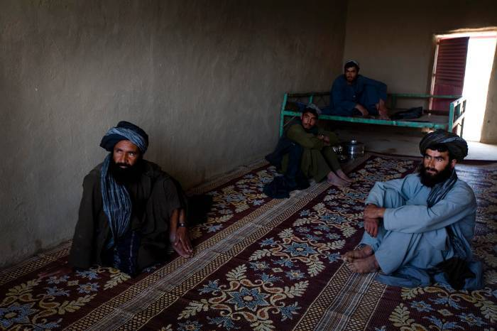 Local men sit in a shop front in Lakari Bazaar, Helmand Province, Afghanistan on the 29th March, 2010. Kate Holt.