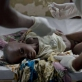 A young boy, who is suffering from cholera, is treated by a doctor and nurse in a cholera treatment center. Kate Holt.