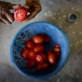 Sakidada, 70 years old and from the Hazari Region of Afghanistan, chops tomatoes for him and his wife. Kate Holt.