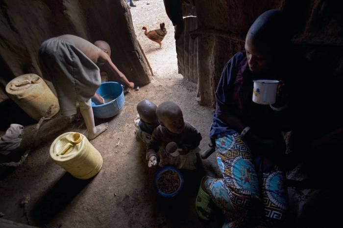 Baby Larumbe washes herself while her cousins eat breakfast around her at her family's compound. Kate Holt.