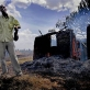 A man stands in front of his burning house, holding a panga. Kate Holt.