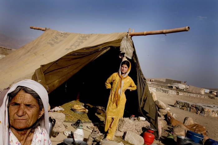 Noorbibi poses for a photograph with one of her daughters outside her shelter. Kate Holt.
