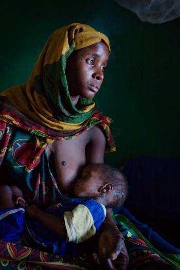 A woman holds her sleeping child in a Therapeutic Feeding Centre supported by UNICEF. Kate Holt.