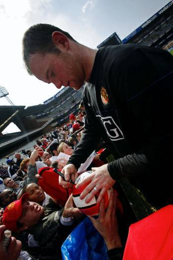 Wayne Rooney, from Manchester United, signs autographs for young fans after a pre match practise. Kate Holt.
