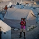 A woman holds her child in front of rows of tents at a camp for displaced people in Port au Prince. Kate Holt.
