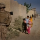 Young children walk down a street that is being patrolled by US Marines in Garmsir. Kate Holt.