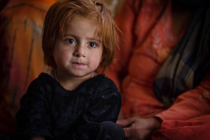 A young girl sits with her mother at a weekly health shura that is organised by a community based educator (CBE). Kate Holt.