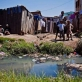 Children stand in front of a muddy stream that runs in front of their house in Antananarivo. Kate Holt.