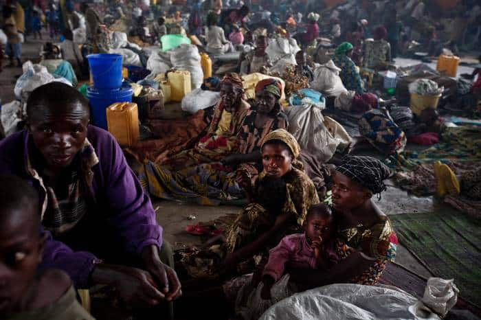 Families displaced by ongoing fighting wait to cook their evening meal. Kate Holt.