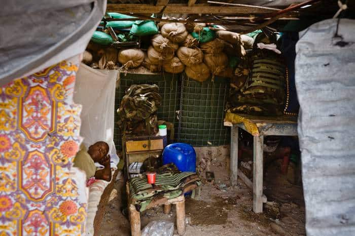 A soldier from Burundi rests on his bed in a bunker on the frontline while his colleague mans a gun position. Kate Holt.