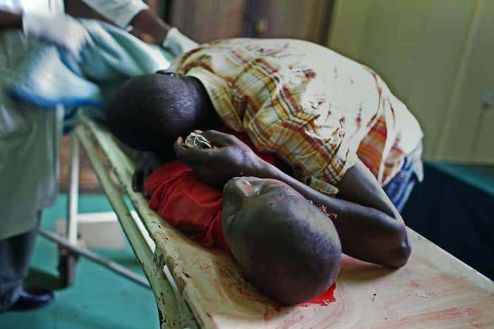 Joshua, cries uncontrollably over the body of his friend, Godfrey Odhiambo, aged 12. Kate Holt.