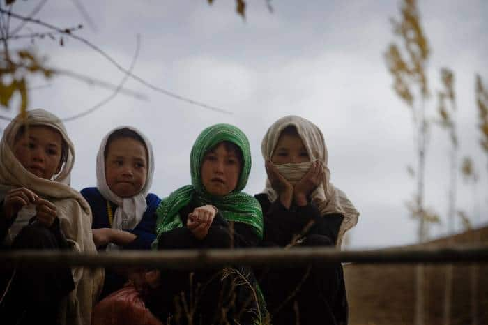 Young girls pose for a photograph near to a water pump installed by Medair. Kate Holt.
