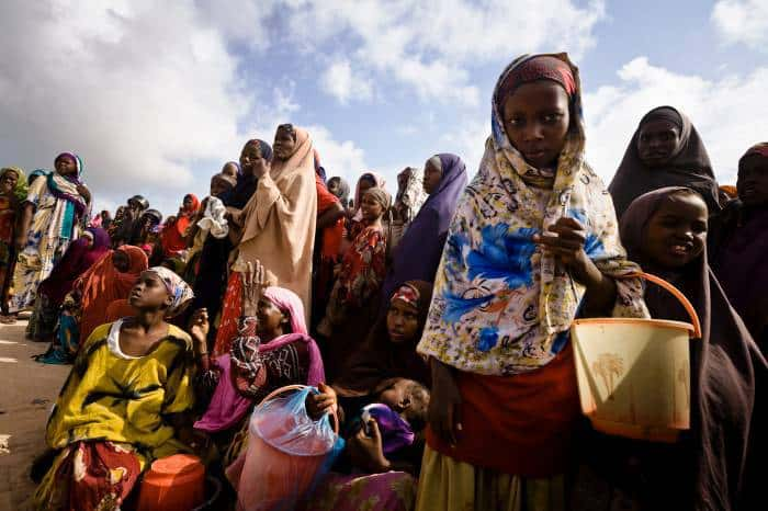 Families queue for food at a feeding point in Badbado camp. Kate Holt.