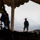 An Afghan Police Officer stands guard at a religious monument while taking part in a joint foot patrol. Kate Holt.