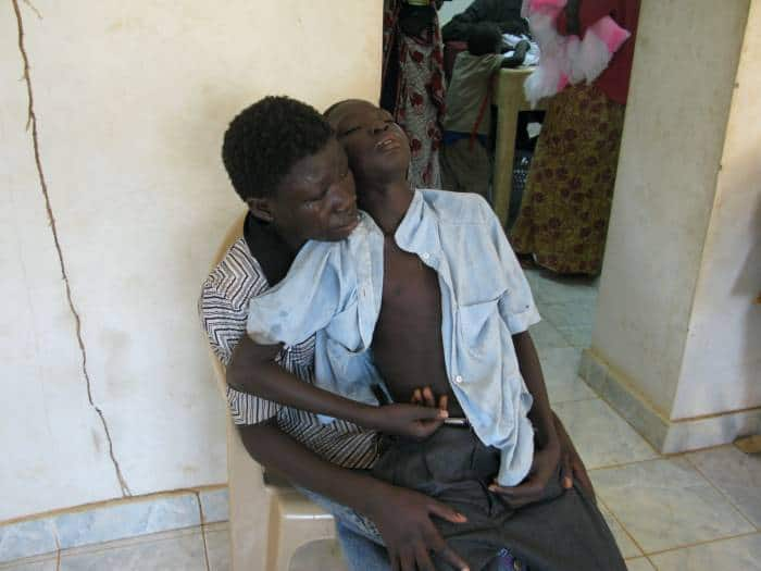 A girl cradles her brother who is suffering from chronic malaria in the Outpatients unit. Kate Holt.