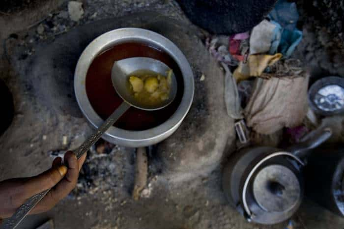 Gulaman cooks a meal for her family of 20 people at their make shift house. Kate Holt.