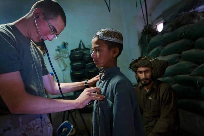 A medical officer for the US Marines examines a young boy in the medical clinic that has been opened for civilians. Kate Holt.