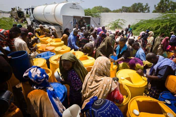 Women and children collect water provided by Ugandan troops. Kate Holt.