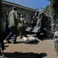 Kenyan police officers unload 16 badly charred bodies from the back of a truck. Kate Holt.